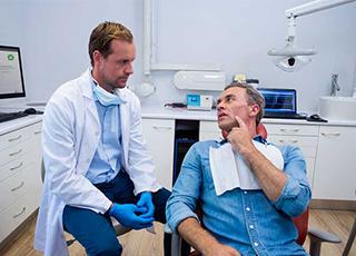 Tandläkare talar med sin klient