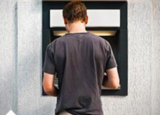 Man tar ut pengar i en bankomat