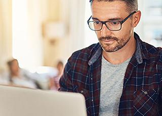 Bild på man som sitter vid sin laptop
