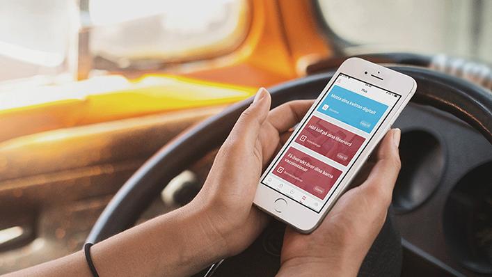 Kvinna sitter i bil och kollar på e-Boks appen