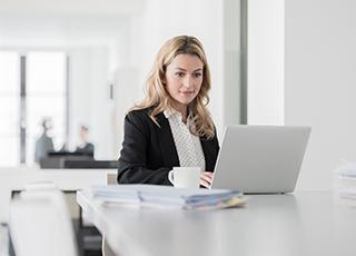 Kvinna sitter vid laptop